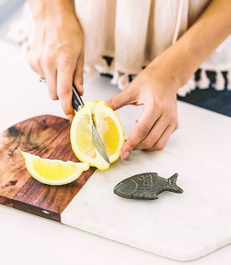 Women cutting lemons with lucky fish on the side